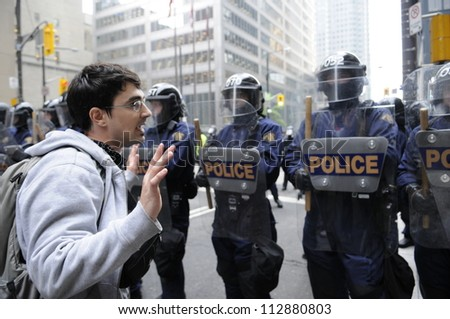 TORONTO-JUNE 26:  A protester raising his hands so as to prove his innocence in front of the riot police during the G20 Protest on June 26, 2010 in Toronto, Canada. - stock photo
