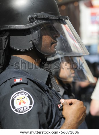 TORONTO-JUNE 25:  A Toronto Police  officer fixing his name tag during  the G20 Protest on June 25, 2010 in Toronto, Canada. - stock photo