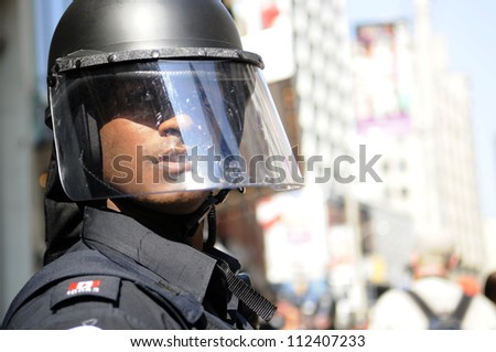 TORONTO-JUNE 25: A Toronto police officer keeping an eye on the people during the G20 Protest on June 25, 2010 in Toronto, Canada. - stock photo