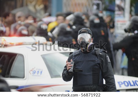 TORONTO-JUNE 26:  A Toronto Riot Police officer with his gas mask on, photographing the protesters  during the G20 Protest on June 26, 2010 in Toronto, Canada. - stock photo