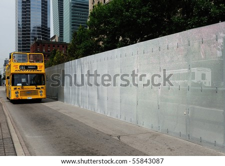 TORONTO-JUNE 23: A tour bus passes near a 3 meter high steel wire fence on June 23, 2010 in Toronto. The fence is in preparation for the upcoming G20 Summit. - stock photo