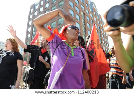 TORONTO-JUNE 25:   An angry afro- american woman chanting slogans in front of a police vehicle during the G20 Protest on June 25, 2010 in Toronto, Canada. - stock photo
