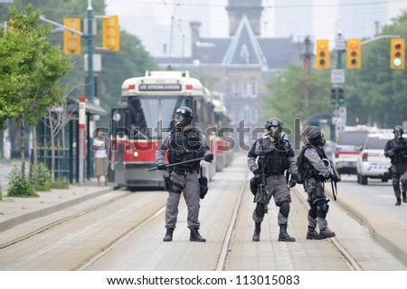 TORONTO-JUNE 27:  Elite  police personnel with gas masks protecting the street car tracks  during the G20 Protest on June 27, 2010 in Toronto, Canada. - stock photo