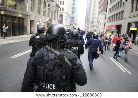 TORONTO-JUNE 26:   Elite riot police officers  marching along the streets during the G20 Protest on June 26, 2010 in Toronto, Canada. - stock photo