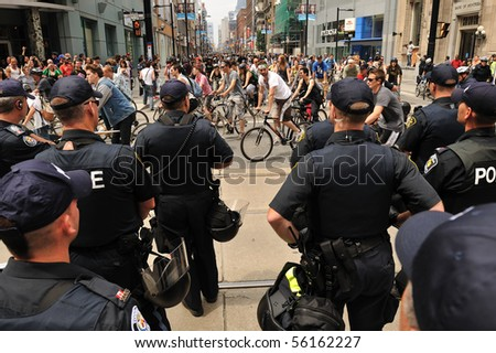 TORONTO-JUNE 27: Large number of Toronto police force block street to prevent 500 protesters on bicycles going close to G20 Convention Centre June 27, 2010 in Toronto. - stock photo