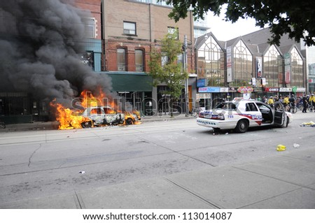 TORONTO-JUNE 26:  Police cars on queen street- one burning another one vandalized  during the G20 Protest on June 26, 2010 in Toronto, Canada. - stock photo