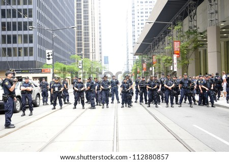 TORONTO-JUNE 27:   Police officers protecting the core downtown  by forming human barricades during the G20 Protest on June 27, 2010 in Toronto, Canada. - stock photo
