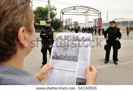 TORONTO-JUNE 27: Protester in front of the Toronto Film Studios reads the latest news update from protest organizers at G20 protest on June 27, 2010 in Toronto. - stock photo