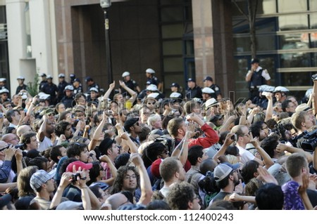 TORONTO-JUNE 28:   Protesters taking pictures during a protest rally in front of the police headquarter after the G20 summit on June 28, 2010 in Toronto, Canada. - stock photo