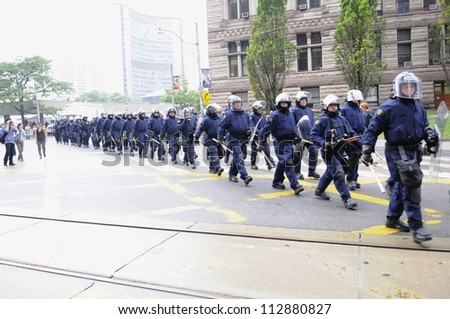TORONTO-JUNE 26:  Riot police group marching on the streets  after a police car was torched nearby during the G20 Protest on June 26, 2010 in Toronto, Canada. - stock photo