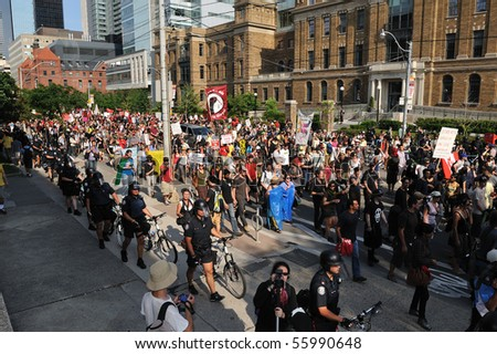TORONTO-JUNE 25: Thousands activists march along the College street of downtown Toronto while participating in a protest ahead of the G20 summit on June 25, 2010 in Toronto, Canada. - stock photo
