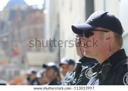TORONTO-JUNE 25:  Toronto police cops keeping an eye on the mob while standing on the sidewalk during the G20 Protest on June 25, 2010 in Toronto, Canada. - stock photo