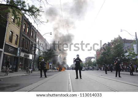 TORONTO-JUNE 26:  Toronto police officers guarding a torched police car while people  gathers around on during the G20 Protest on June 26, 2010 in Toronto, Canada. - stock photo