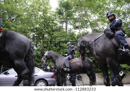 TORONTO-JUNE 27:   Toronto police officers on horses patrolling the streets during the G20 Protest on June 27, 2010 in Toronto, Canada. - stock photo