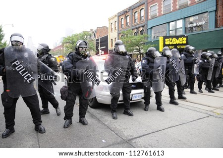 TORONTO-JUNE 26:   Toronto riot police officers protecting the entrance of queen street through spadina during the G20 Protest on June 26 2010 in Toronto, Canada. - stock photo