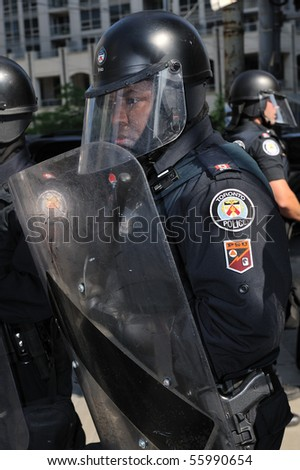 TORONTO-JUNE 25: Toronto Riot Police restrict protesters movement away from G20 Summit at Convention Centre on June 245 2010 in Toronto, Canada. - stock photo