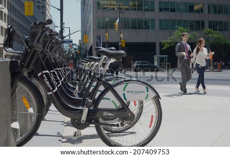 TORONTO - JUNE 27: Two people walk past a rental station in Toronto, shown June 27, 2014. The three-year old service has 800 bicycles and 80 stations in downtown Toronto. - stock photo