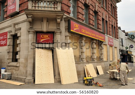 TORONTO-JUNE 27: Workers put plywood on CIBC bank windows for protection of violent protesters at upcoming G20 protest on June 27, 2010 in Toronto. - stock photo