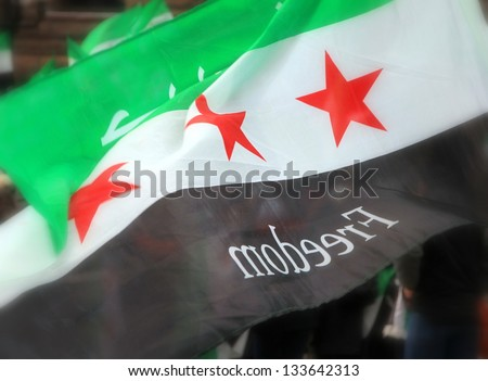 TORONTO-MARCH 16: A protester waiving a Syrian flag during a protest rally organized to raise awareness and commemorate two years of Syrian revolution on March 16, 2013 in Toronto, Canada. - stock photo