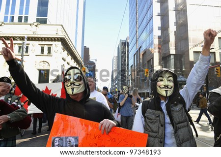 "TORONTO -MARCH 11: Activists with guy fawkes mask during a protest against the ""robocalls scandal"" -a kind of election fraud from last year'Â?Â?s federal election on March 11 2012 in Toronto,Canada. - stock photo"