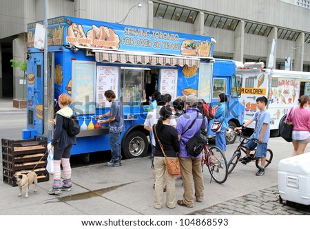 TORONTO - MAY 27: A truck selling street food on May 27, 2012 in Toronto. Before a street food truck can be put to use, it must meet the requirements of the Ontario Food Premises Regulation 562/90. - stock photo
