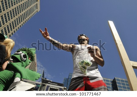TORONTO - MAY 5: Marijuana activists throwing marijuana pouches towards the crowd during the 14th annual Global Marijuana March on May 5  2012 in Toronto, Canada. - stock photo