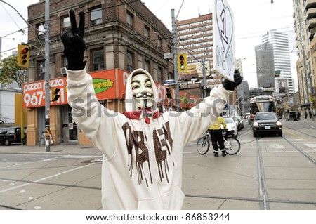 TORONTO - OCTOBER 17: A protestor wearing a guy fawkes mask walking in a rally in front of a piza pizza store  during the Occupy Toronto Movement on October 17, 2011 in Toronto, Canada. - stock photo