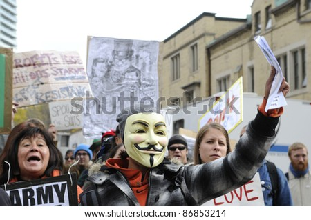 TORONTO - OCTOBER 17: Angry protestors  walking in a rally  during the Occupy Toronto Movement on October 17, 2011 in Toronto, Canada. - stock photo