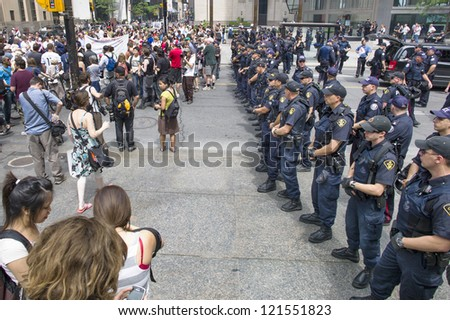 TORONTO, ON/CANADA - JUNE 27, 2010:  G20 Protesters gather in from of riot police on June 27, 2010 in Toronto - stock photo