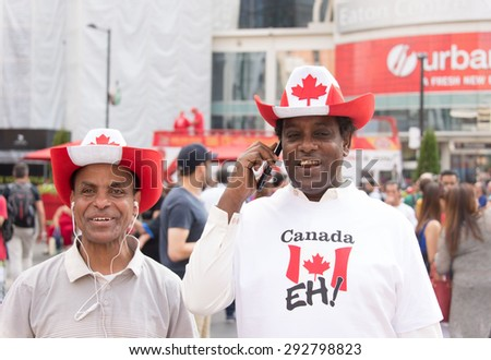 TORONTO,ONTARIO-JULY 1,2015: Canada Day celebrations in Toronto: Afro American immigrant to multicultural city wearing the Canadian flag colors in Dundas Square - stock photo