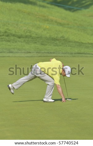 TORONTO, ONTARIO - JULY 21:English golfer Paul Casey picks up his ball after putting during a pro-am event at the RBC Canadian Open golf on July 21, 2010 on Toronto, Ontario. - stock photo