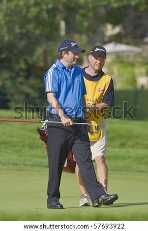 TORONTO, ONTARIO - JULY 21: South African golfer Tim Clark walks off a green during a pro-am event at the RBC Canadian Open golf on July 21, 2010 in Toronto, Ontario. - stock photo