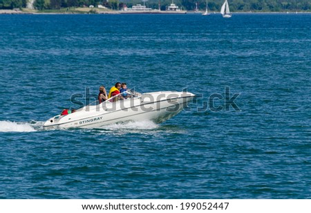 TORONTO, ONTARIO - JUNE 15, 2014: Family in a fast power boat cruising on Lake Ontario along the shoreline. - stock photo