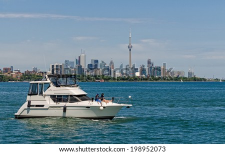 TORONTO, ONTARIO - JUNE 15, 2014: Luxury boat against the skyline of Toronto with CN Tower and other highrise buildings - stock photo
