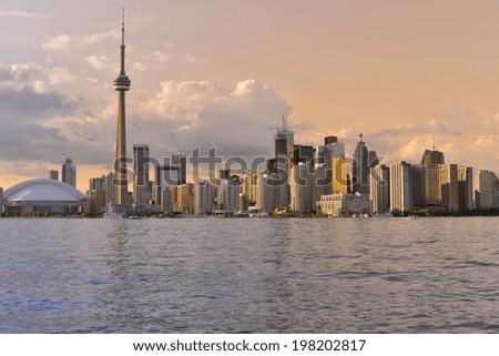 Toronto Skyline at sunset over lake Ontario with colorful sky - stock photo