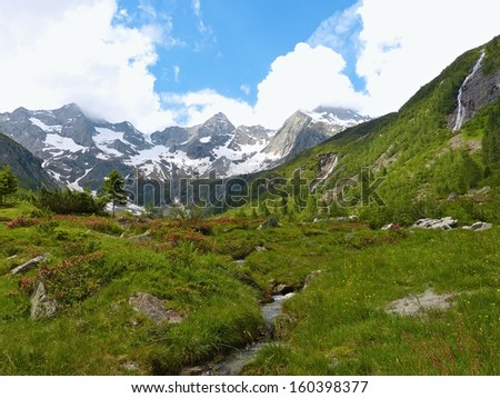 Torrent in the high mountains and glacier in the background - stock photo
