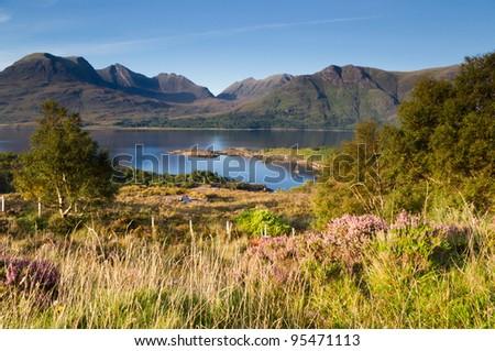 Torridon mountains over Torridon loch / Bright sunny day at Torridon loch and mountain range - stock photo