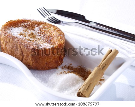 Torrijas � French Toast.  Torrijas are the spanish version of French Toast. Slices of Bread soaked in milk,  egg-coated and fried. Served with sugar and cinnamon. Typical dessert in Easter Season. - stock photo