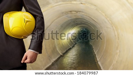 torso engineer hand holding yellow helmet for workers security against the background of  Empty sewer channel dark interior flowing dirty water in perspective canalization - stock photo
