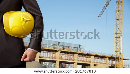 torso engineer hand holding yellow helmet for workers security on background of new highrise apartment buildings and construction cranes on blue sky background  Crane lifts load - stock photo