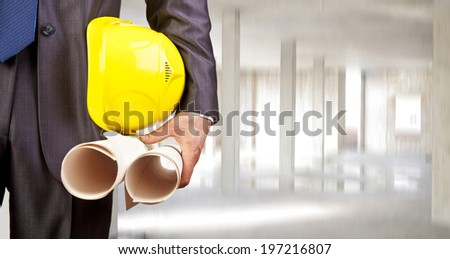 torso engineer holding yellow helmet for workers security and two blueprint over empty new building inside concrete beam in house background Copy Space for inscription - stock photo