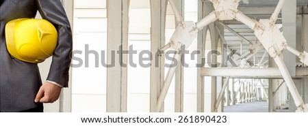 torso engineer or worker hand holding yellow helmet for workers security over empty new modern building inside perspective house background Empty Copy Space for inscription Idea of concept of safety - stock photo