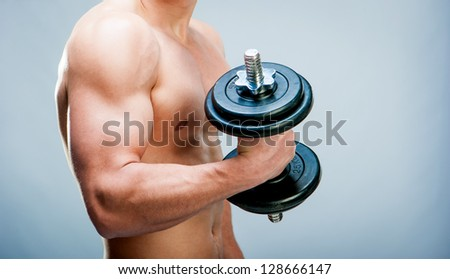 Torso Muscular man with dumbbells on a gray background - stock photo