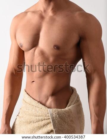Torso of a male bodybuilder in a towel - stock photo