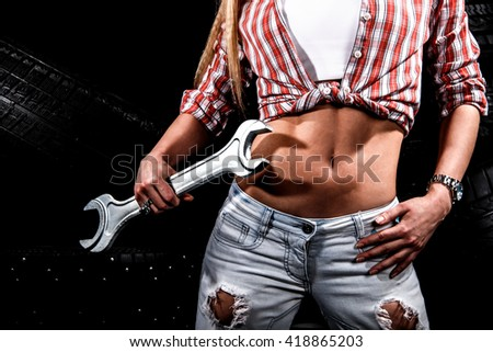Torso of a sexy woman with a big wrench at the background of tires - stock photo