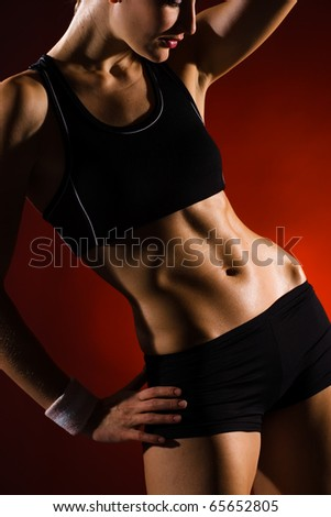 Torso of a young fit woman. Shot in studio on a red background. - stock photo