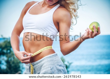 Torso of a young woman with an apple and meter - stock photo