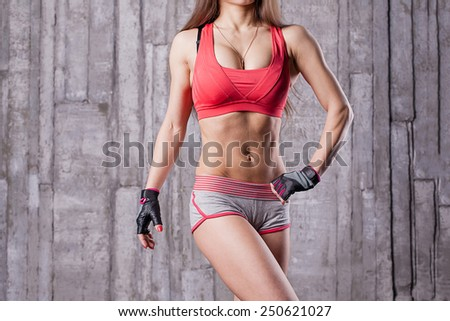Torso of athlette girl in gym - stock photo