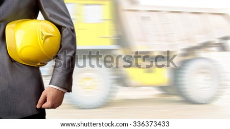 torso of engineer or construction worker hold in hand yellow helmet or plastic hard hat against big truck. Empty copy space for inscription, people or objects. Industrial transportation - stock photo