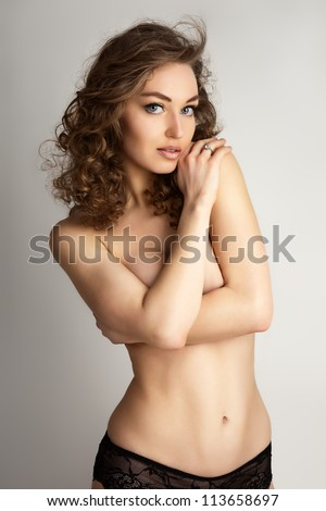 Torso of naked female keeping her arms on breasts over grey background. - stock photo